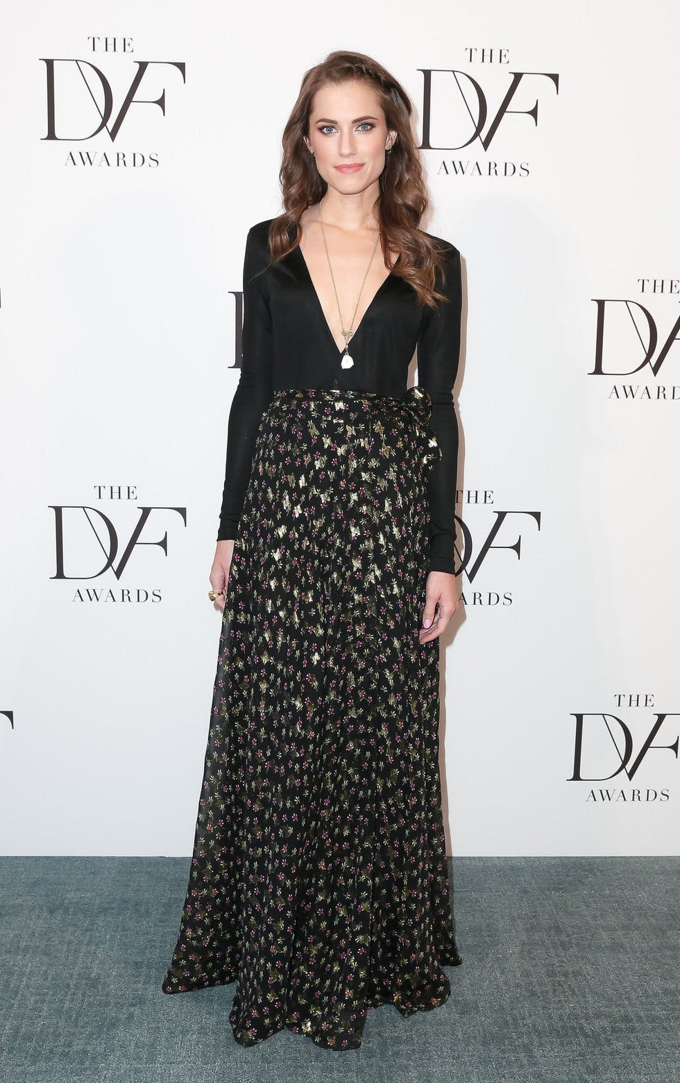 aad4516659 The Girls star turns heads in a plunging black long sleeve top and black  and gold printed maxi skirt both by Diane Von Furstenberg accessorised with  a long ...