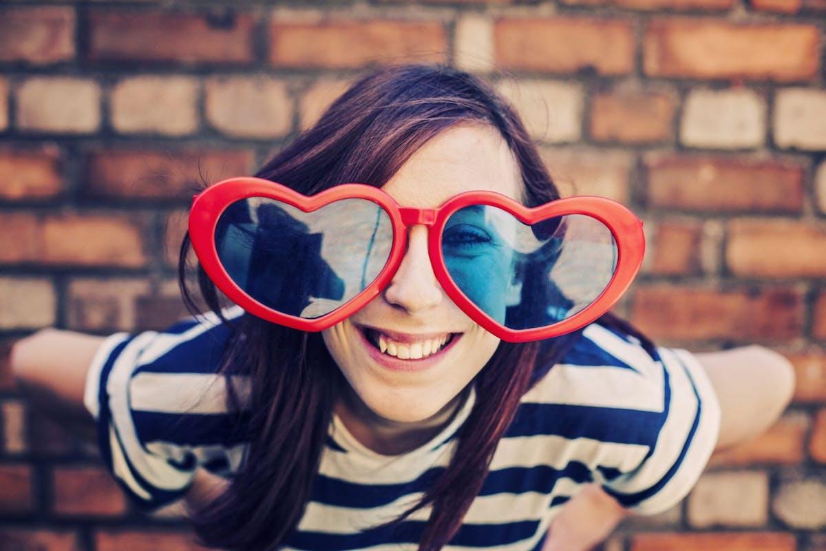 Happy smiling teenage girl wearing oversized heart sunglasses
