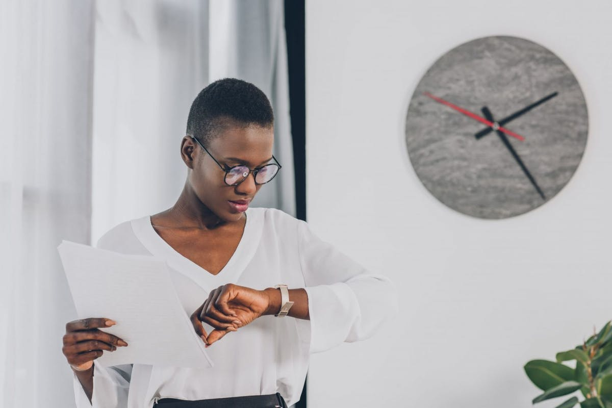 stylish african american businesswoman holding documents and checking time in office, clock on white wall
