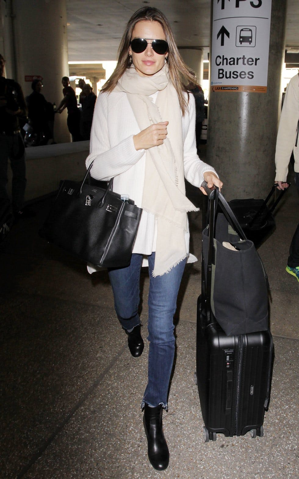 a894fa1efa9 A soft knit in winter white layered with a cream scarf makes for a  luxuriously chic look. Black accessories pop against the soft tones and  frayed denim adds ...
