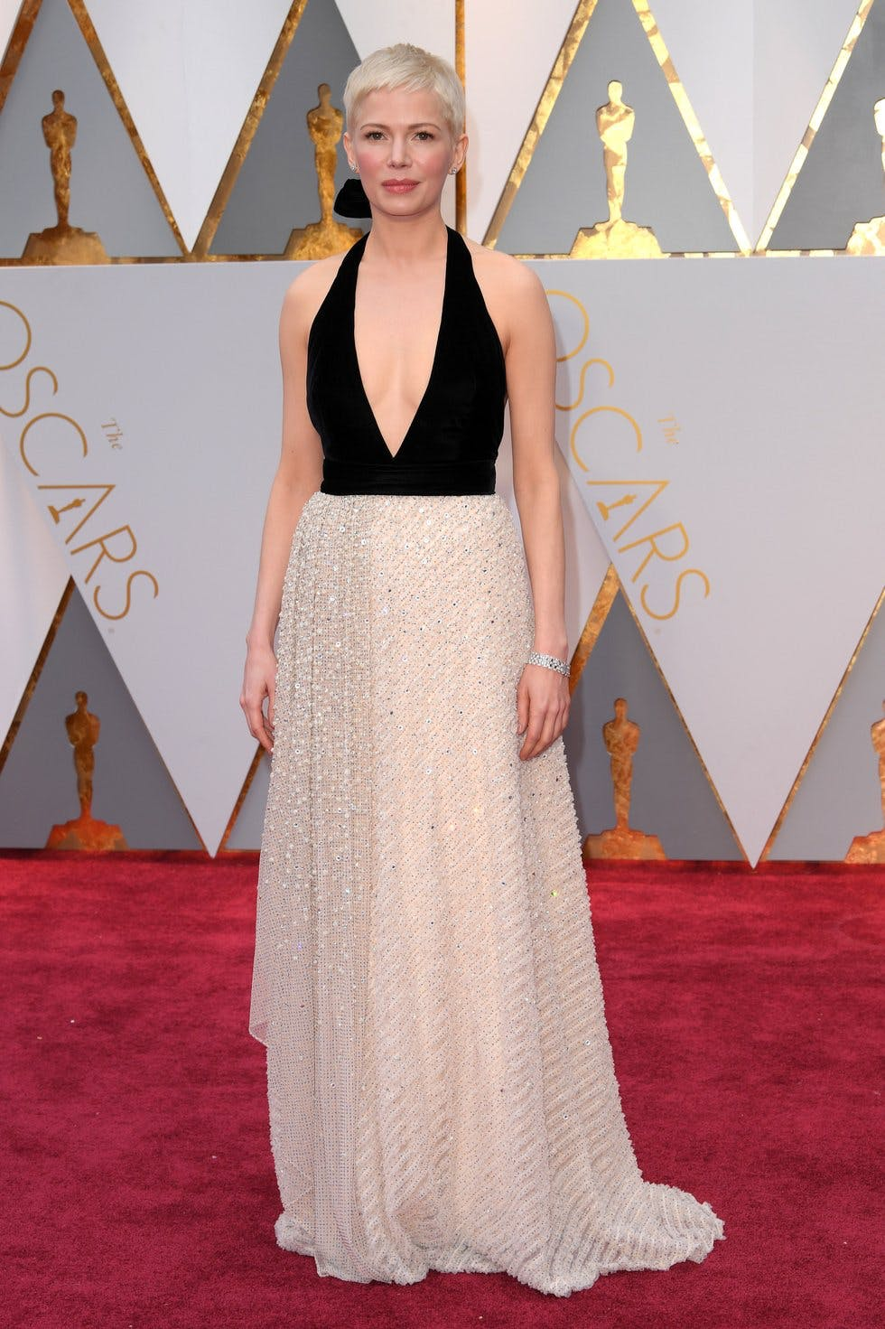f945b99ca Michelle Williams' Louis Vuitton gown gives romance an edge by combining a  pale beaded skirt and deep plunge black top.