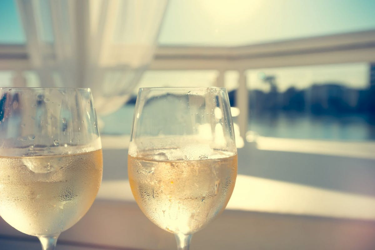 2 glasses of white wine beside a day bed. The day bed has curtains and is waterfront. There is condensation on the wine glasses and they look very refreshing. The sky is cloudless blue with the sun bright. Very romantic and relaxing scene.