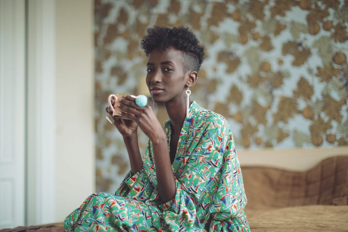 Woman drinking a hot beverage in bed