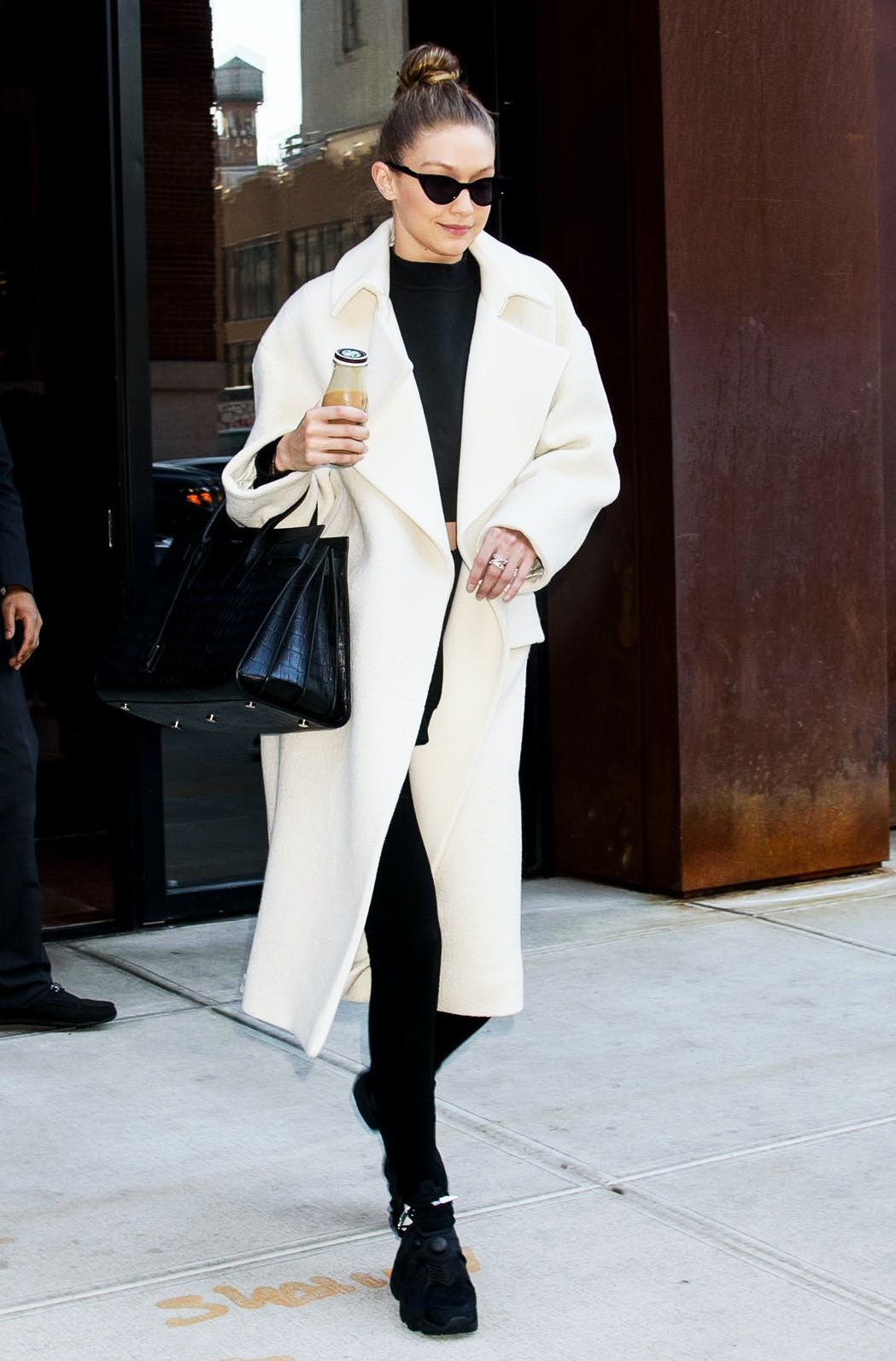 1a709fc55c90 A white coat looks effortlessly elegant worn over an all black outfit. Keep  the contrast running throughout the look by pairing a ladylike handbag and  sharp ...