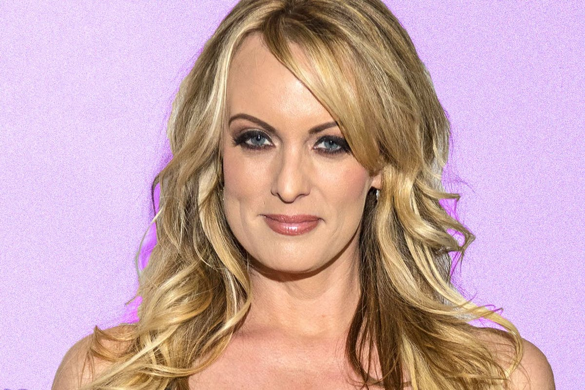 Stormy Daniels smiling against a pink backdrop