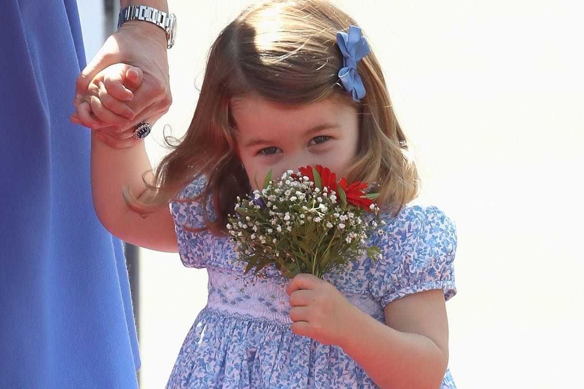 Princess Charlotte sniffs a bouquet of flowers while clasping her mother Kate Middleton's hand