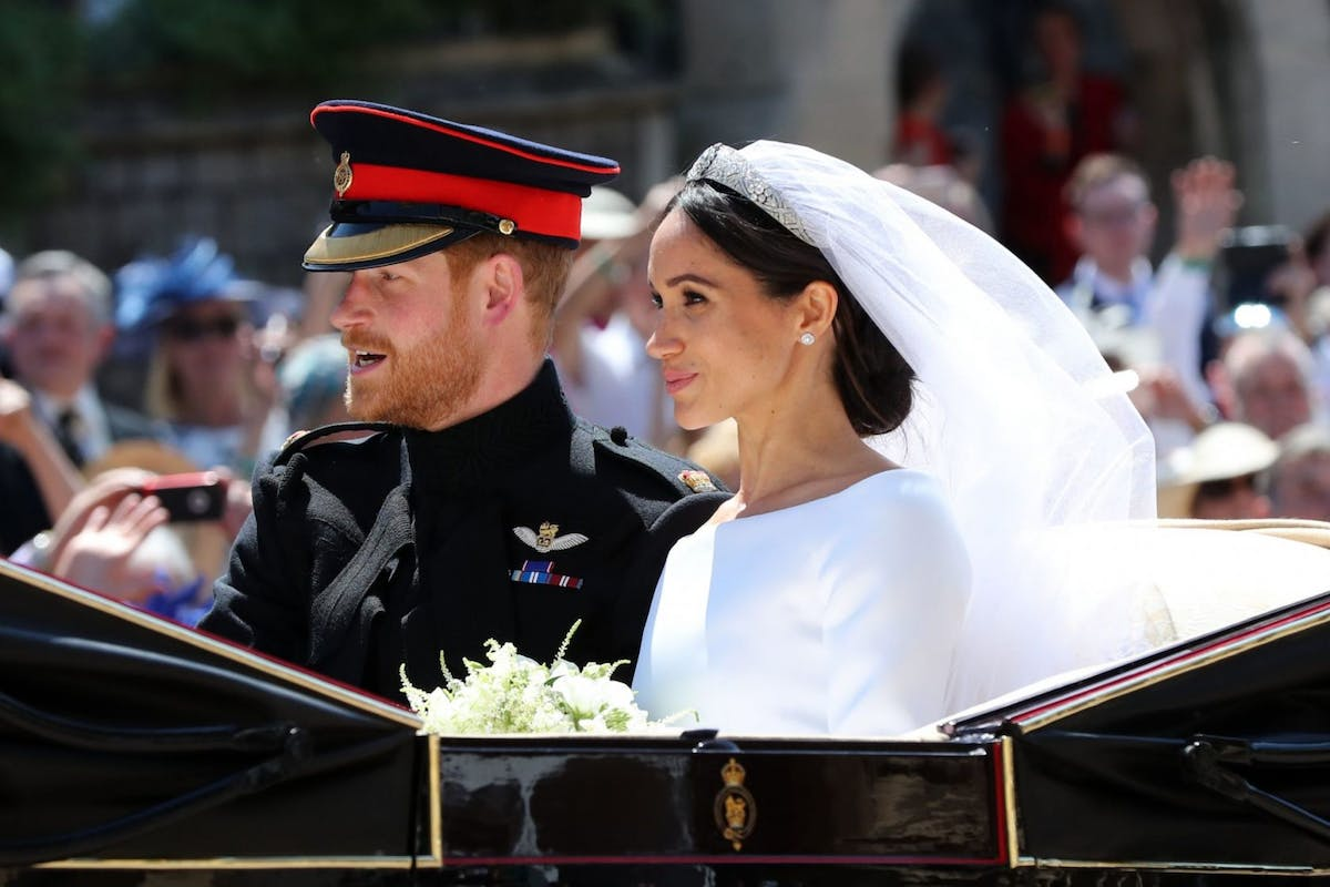 WINDSOR, ENGLAND - MAY 19: Prince Harry, Duke of Sussex and Meghan, Duchess of Sussex leave Windsor Castle in the Ascot Landau carriage during a procession after getting married at St Georges Chapel on May 19, 2018 in Windsor, England. Prince Henry Charles Albert David of Wales marries Ms. Meghan Markle in a service at St George's Chapel inside the grounds of Windsor Castle. Among the guests were 2200 members of the public, the royal family and Ms. Markle's Mother Doria Ragland. (Photo by Gareth Fuller - Pool/Getty Images)