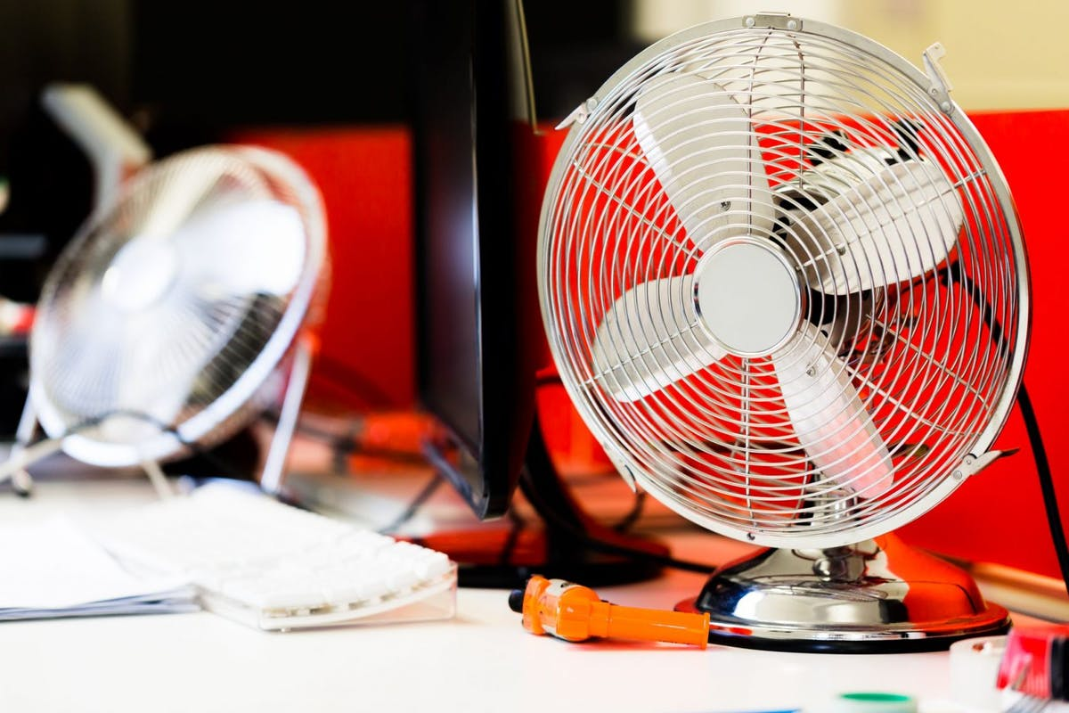 Small, portable switched off fan on desk in office. Horizontal close up, low angle perspective from desk level