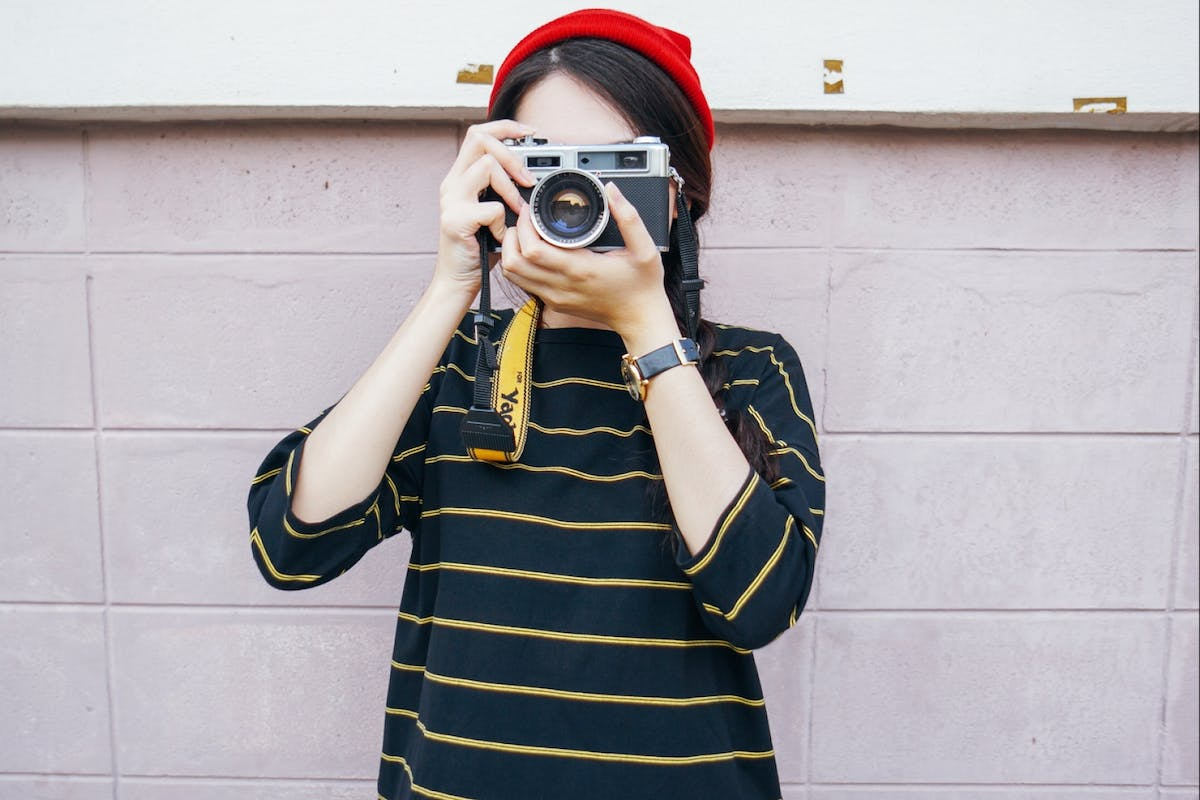 Girl holds film camera to take a picture