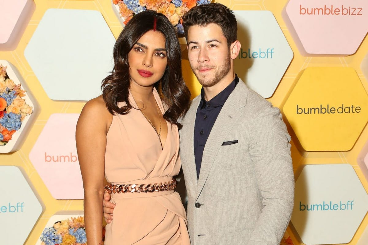 Indian Bollywood actress Priyanka Chopra (L) with her husband US musician Nick Jonas pose for a picture at Bumble's launch party, in New Delhi on December 05, 2018. (Photo by Pallav Paliwal / AFP) (Photo credit should read PALLAV PALIWAL/AFP/Getty Images)