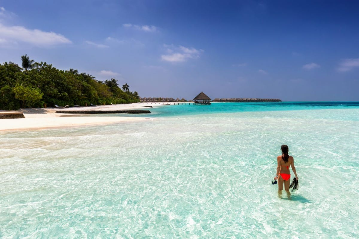 Woman stands in the sea, clutching snorkelling equipment, as she gazes at a Maldives beach