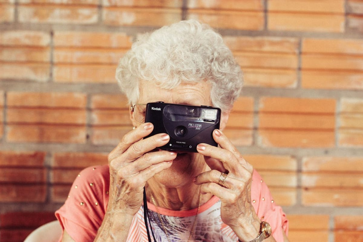 Old woman taking a photo with a film camera