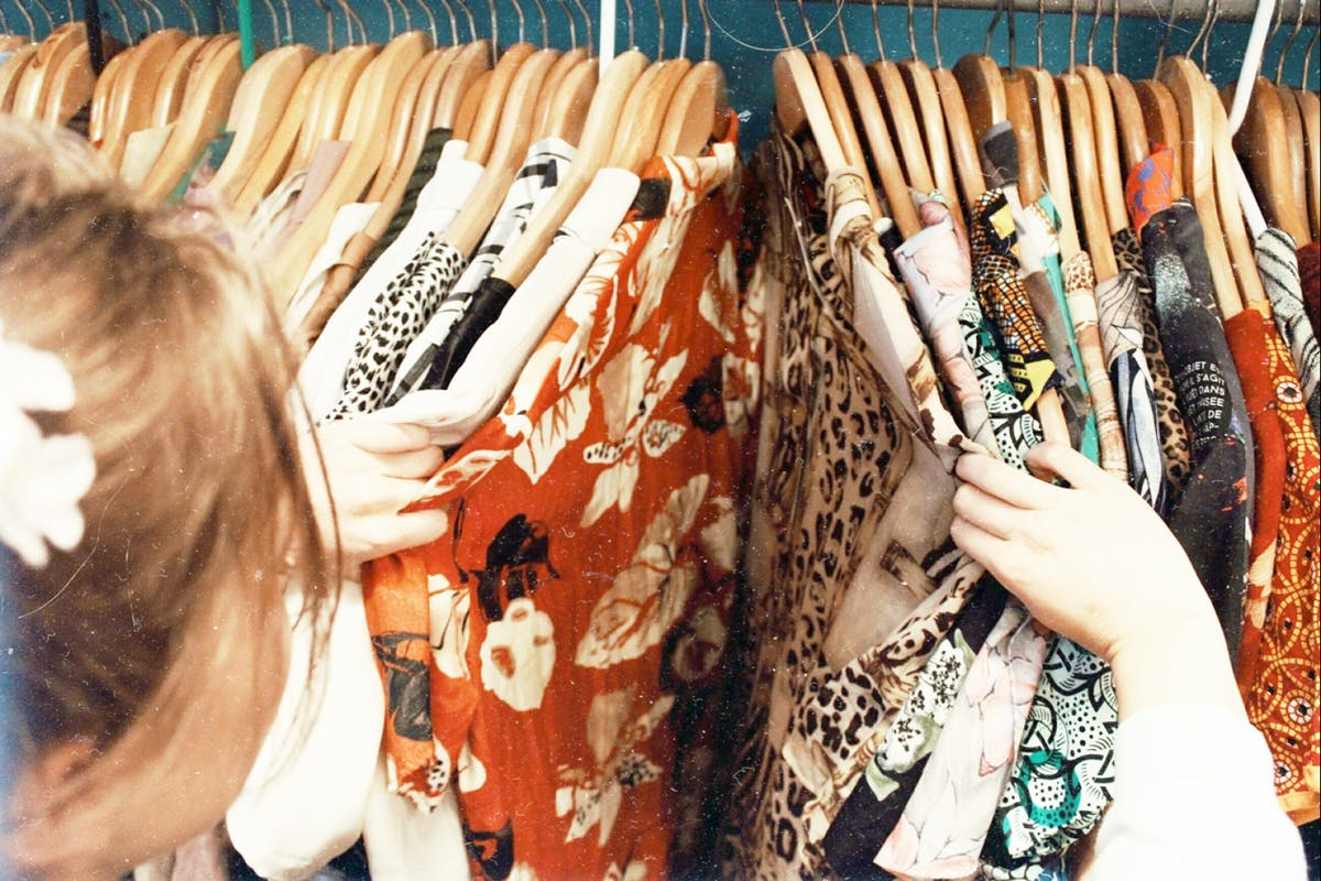 Image of someone sifting through a charity shop rail