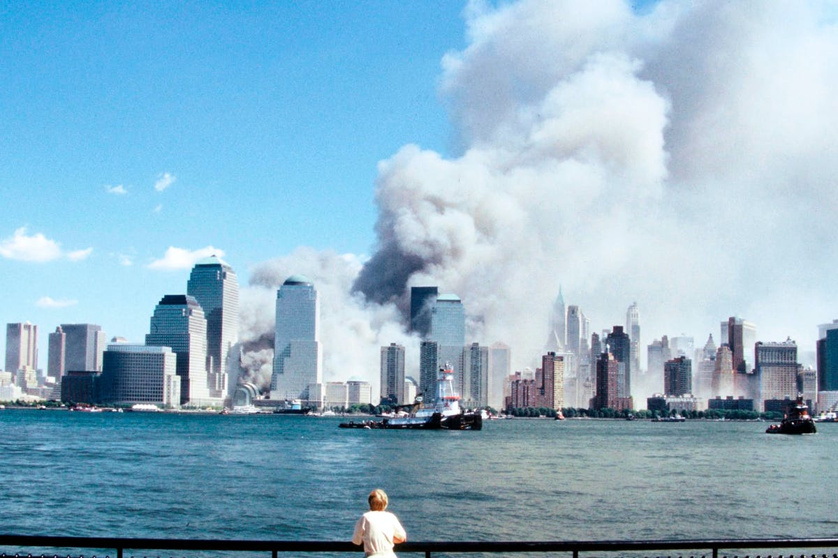 9/11: A shocked bystander watches the World Trade Centre's Twin Towers burn after the deadly attack on 11 September 2001