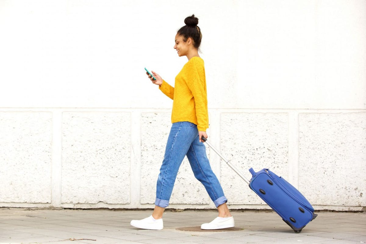 Side view portrait of young woman walking with travel bag and using mobile phone