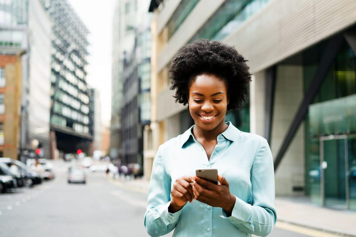 Woman using smart phone in financial district - stock photo