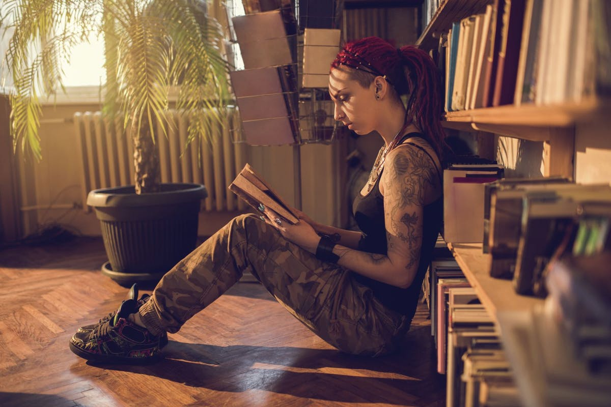 Profile view of a young woman sitting on a floor in a library and reading a book.