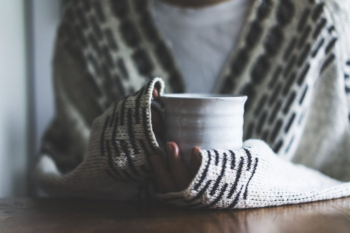 Woman wearing cardigan holding ceramic mug, drinking coffee on a cold day