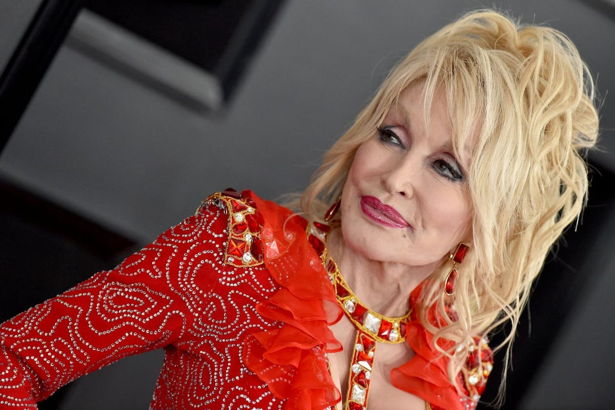 Dolly Parton on the red carpet in a red dress
