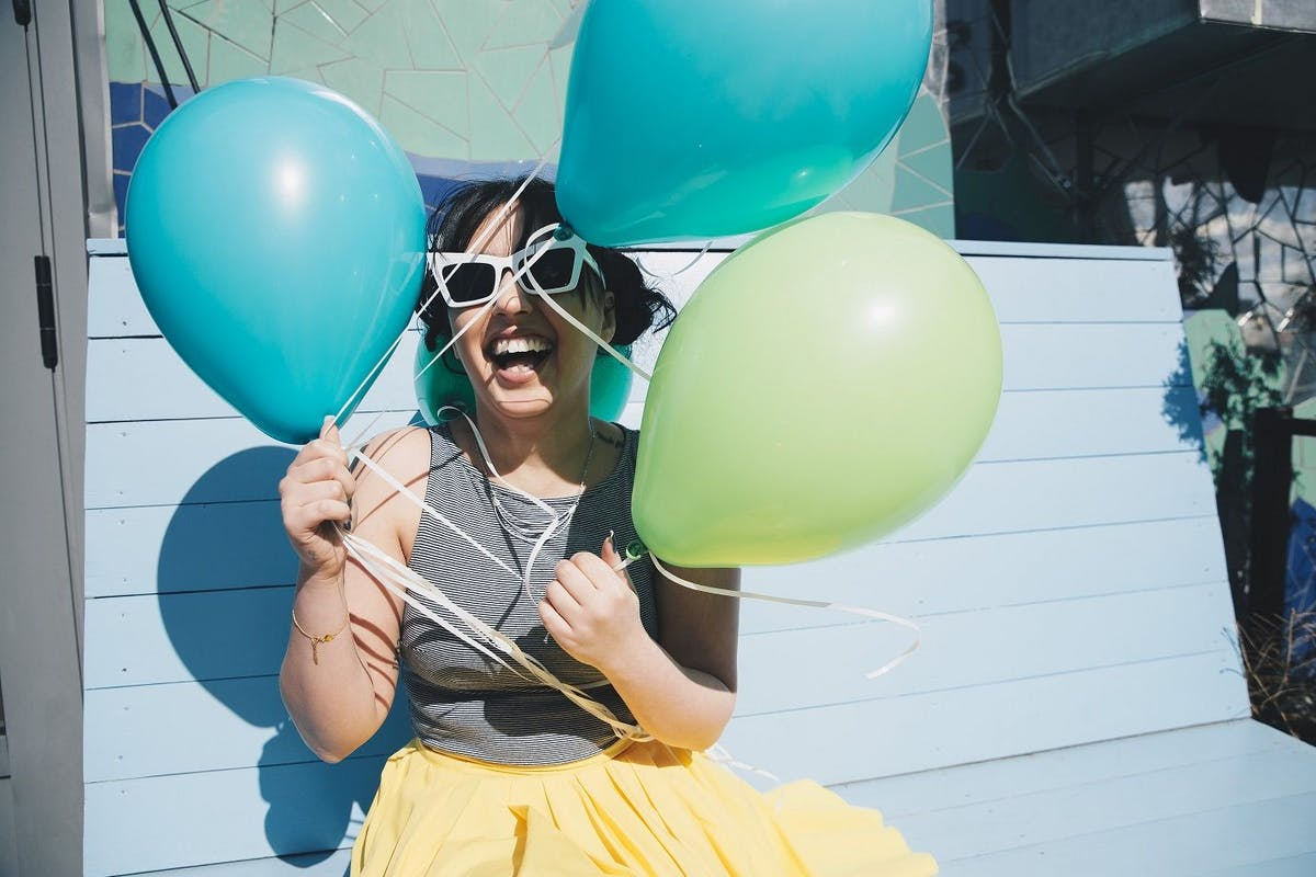 A happy woman holding balloons at a party
