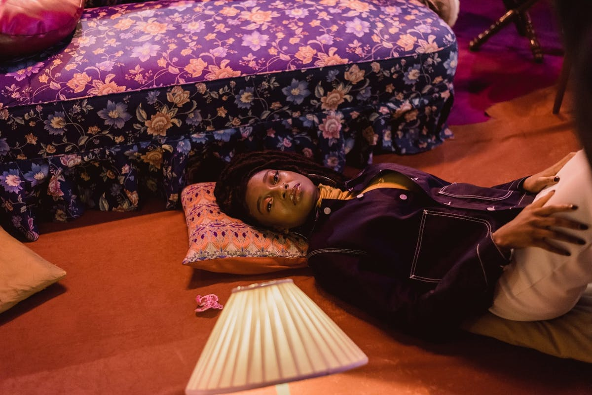 Rapper Little simz lying on the floor with cushions