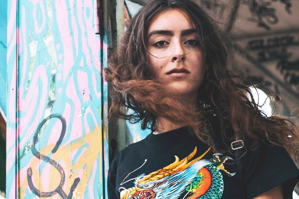 Woman standing next to a wall of graffiti