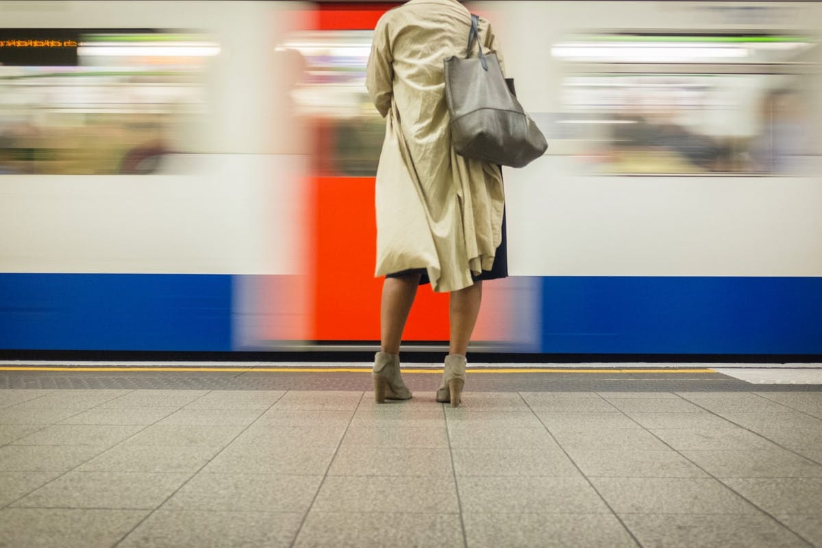 woman standing on a London underground platform in a skirt as a train speeds past
