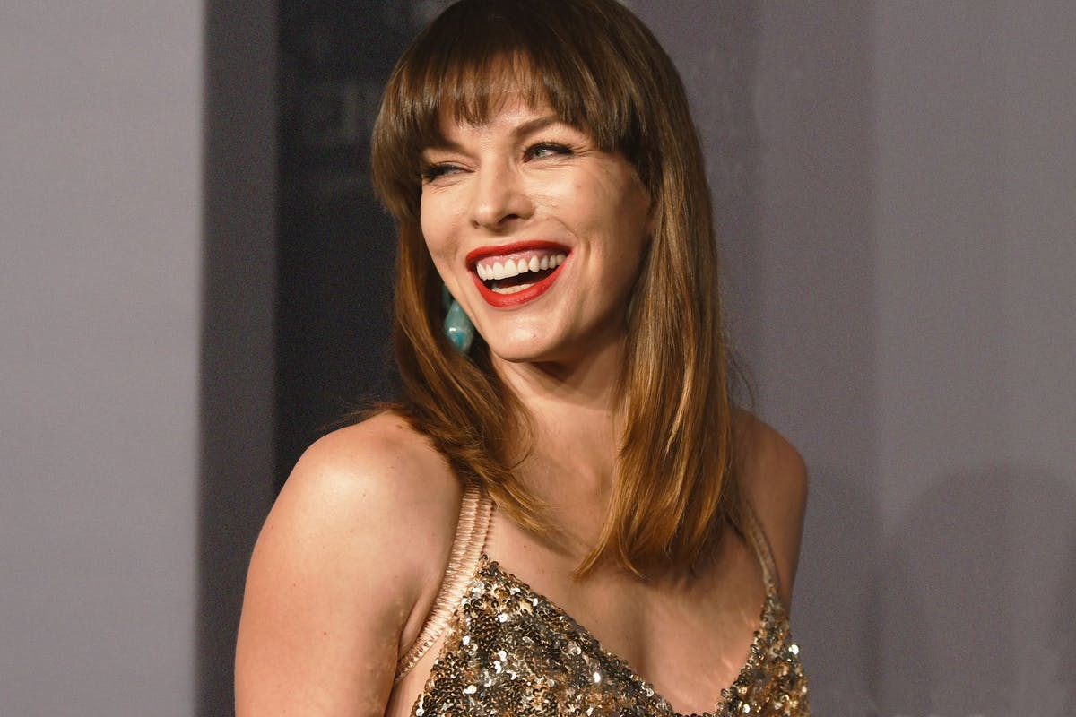Milla Jovovich laughing on the red carpet