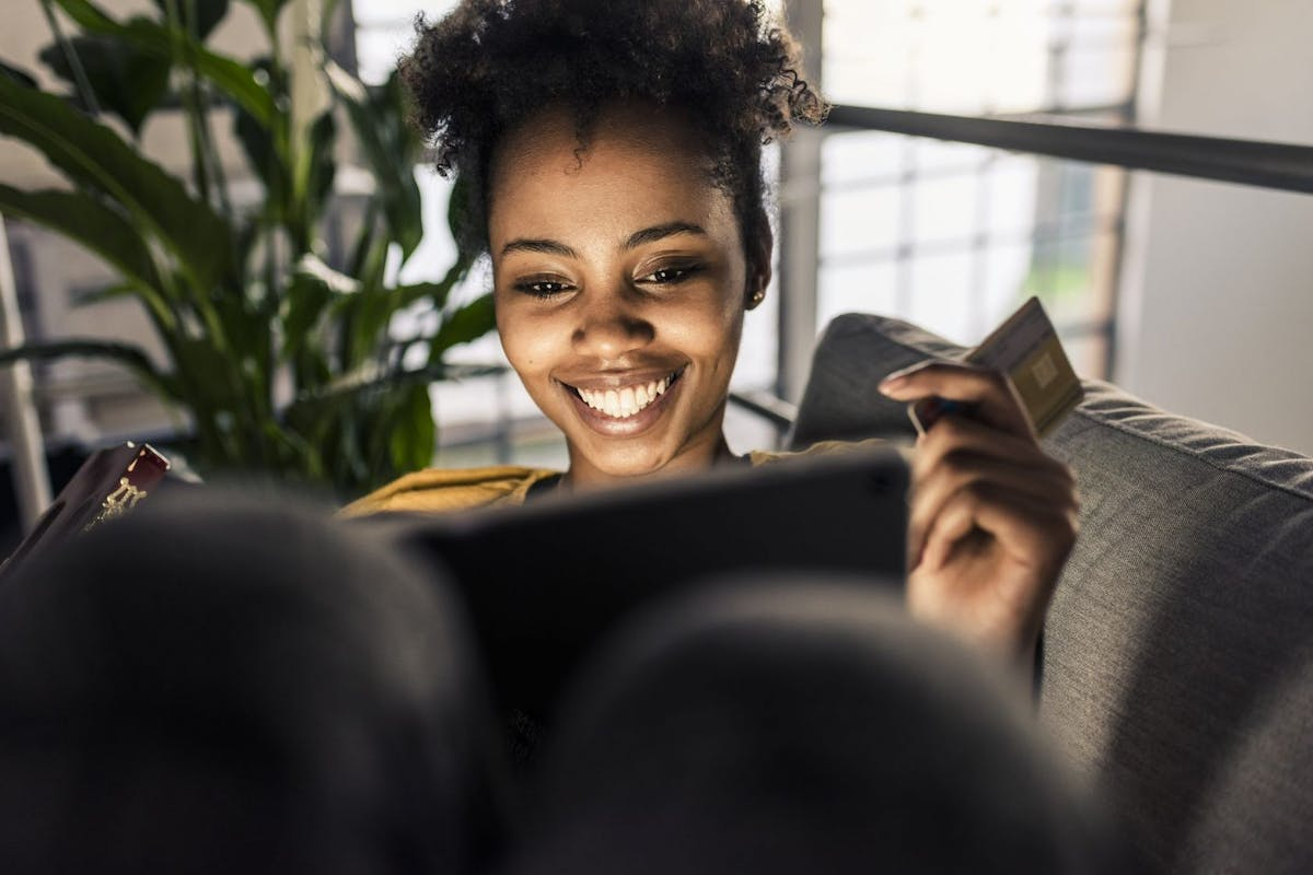 Smiling young woman on couch with credit card and laptop - stock photo