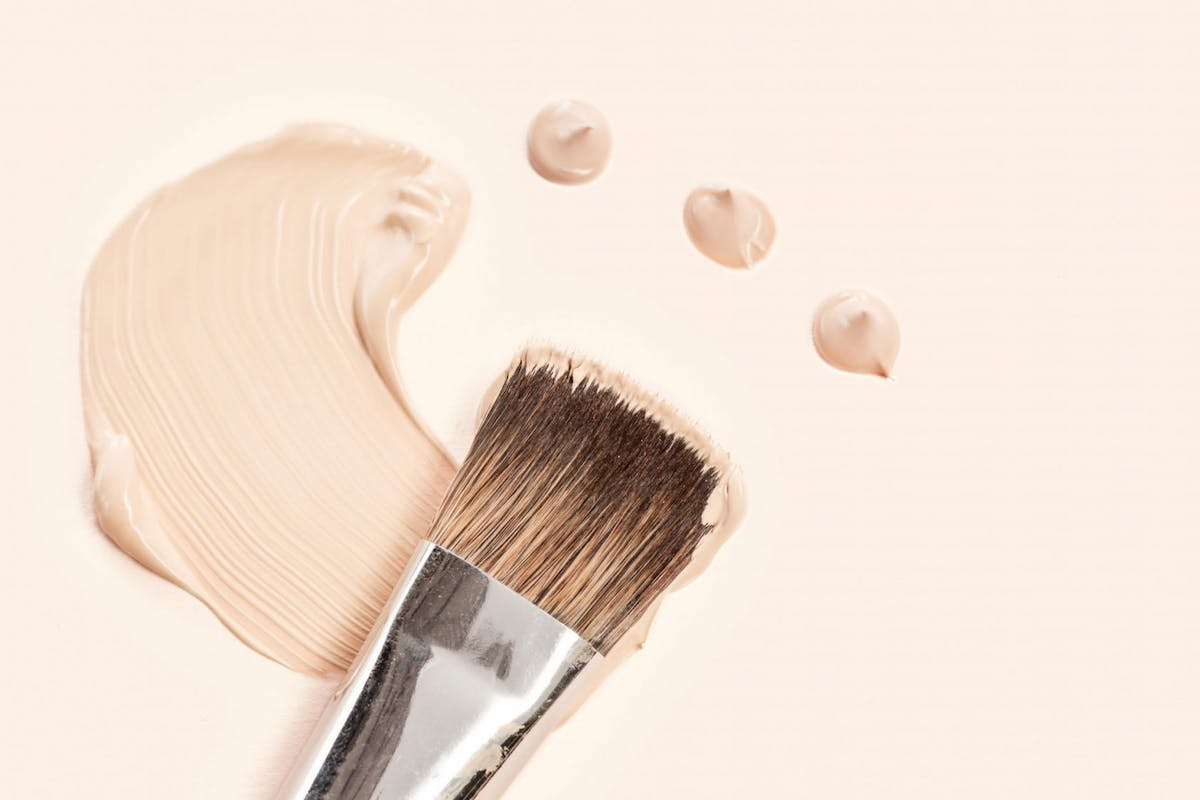 Cosmetic foundation cream and powder with brush on white background