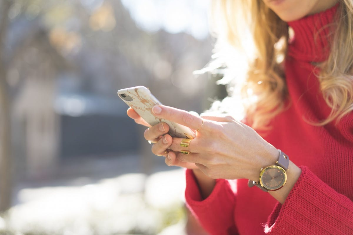 Woman scrolling on her phone in a red jumper and with a watch on her wrist