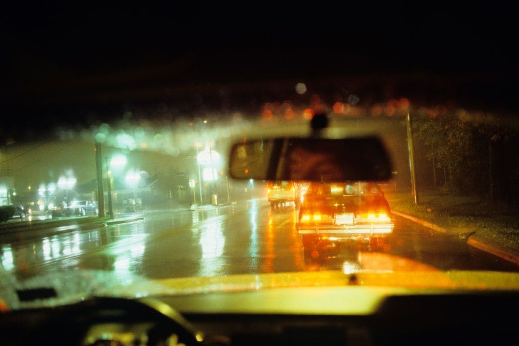 A man driving a taxi at night