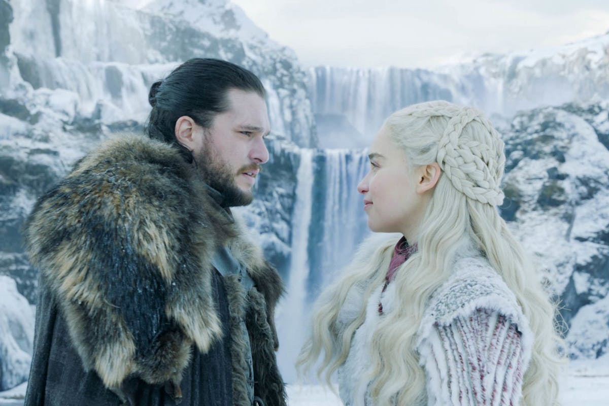 Jon Snow with Daenerys Targaryen with a frozen waterfall behind them