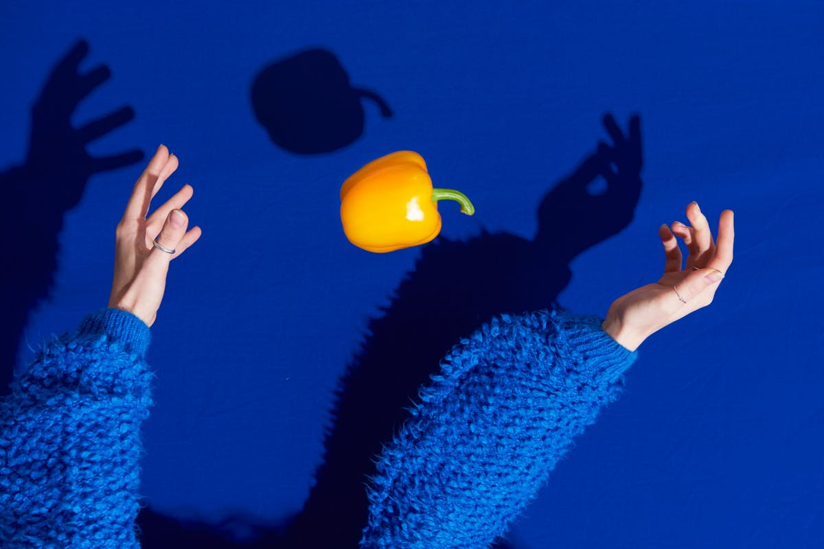 Woman throwing vegetable in air