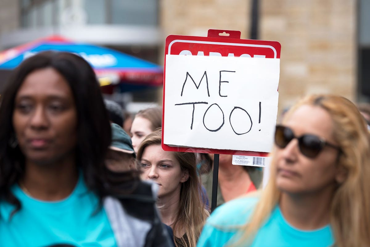 Image of a woman holding a #MeToo placard