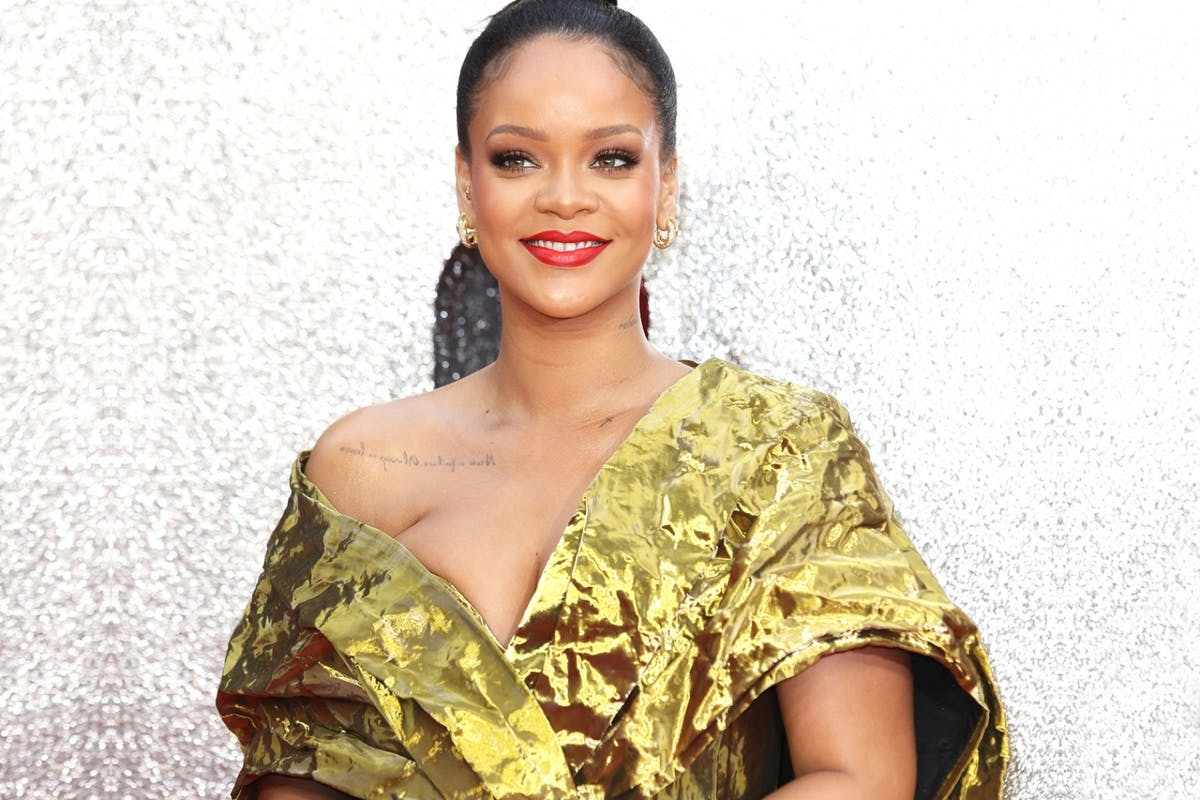 Image of popstar, Rihanna, wearing a yellow dress and red lip/