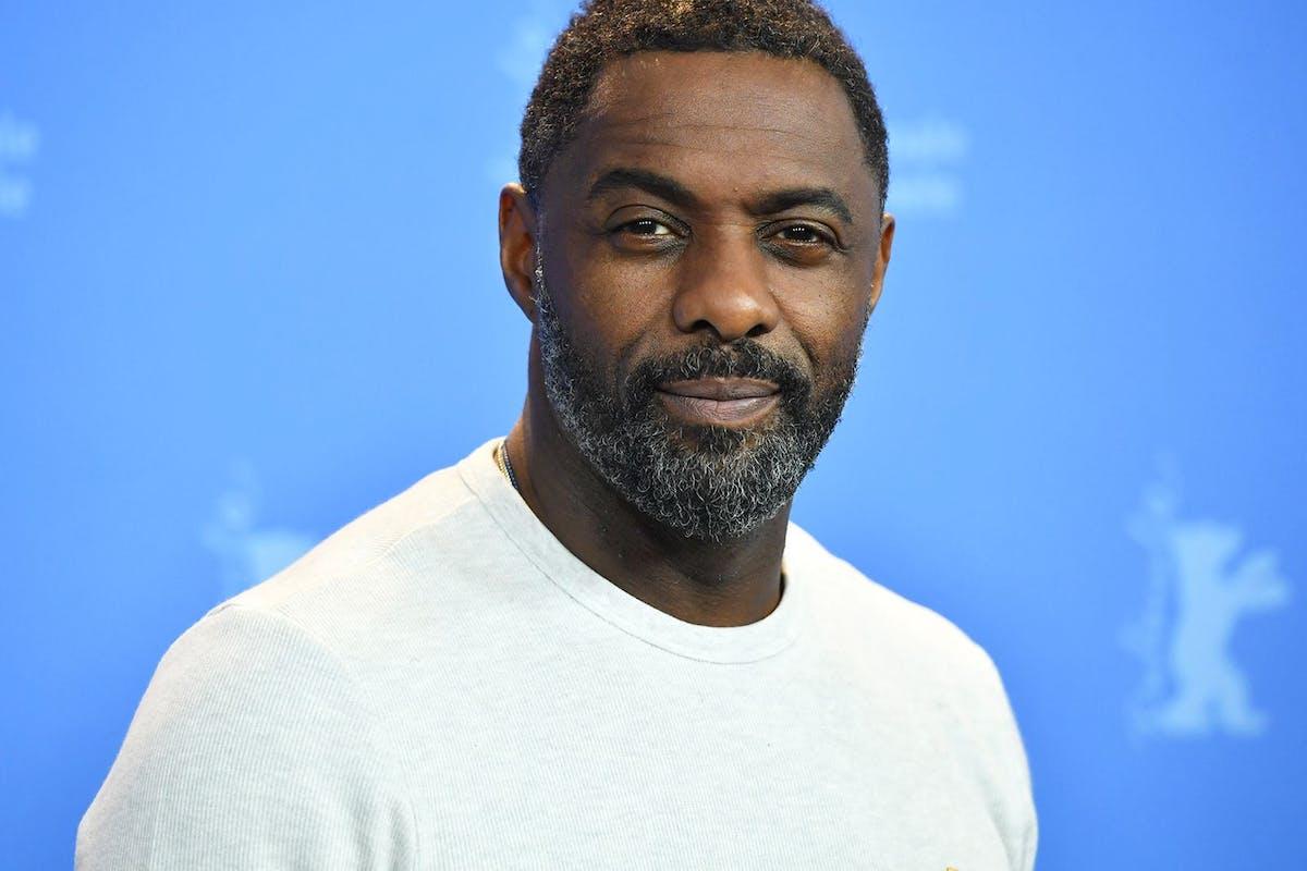 Idris Elba headshot on blue background