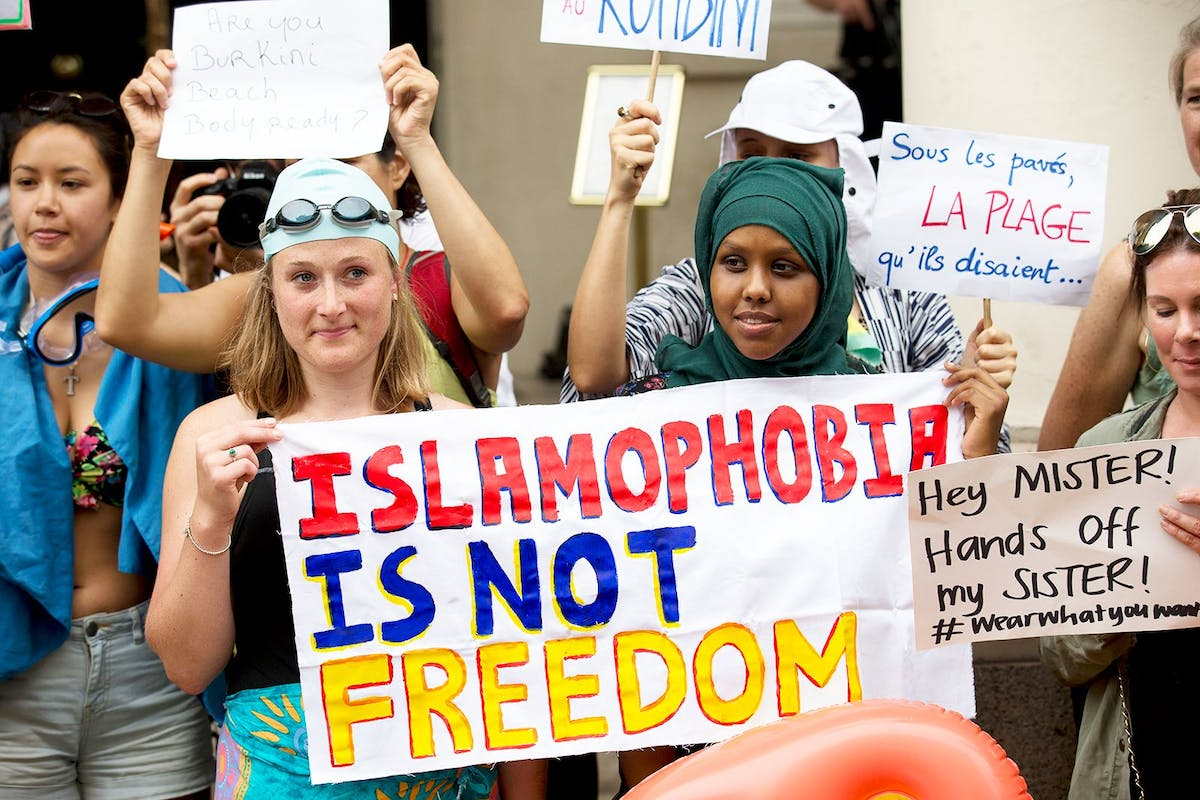 """A group of women protesting and holding a sign that reads: """"Islamophobia is not freedom"""""""