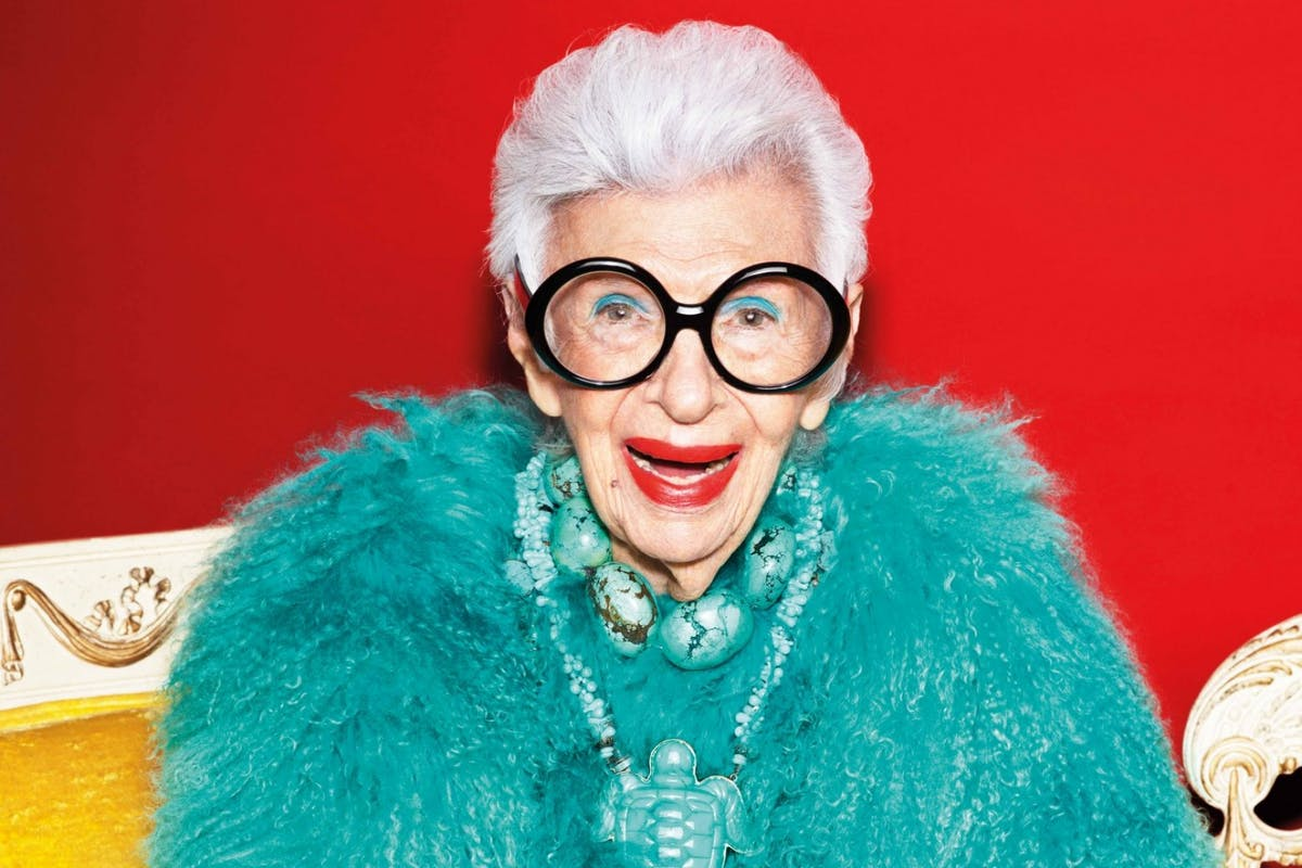 Iris Apfel wearing a turquoise fluffy jacket and smiling for the camera