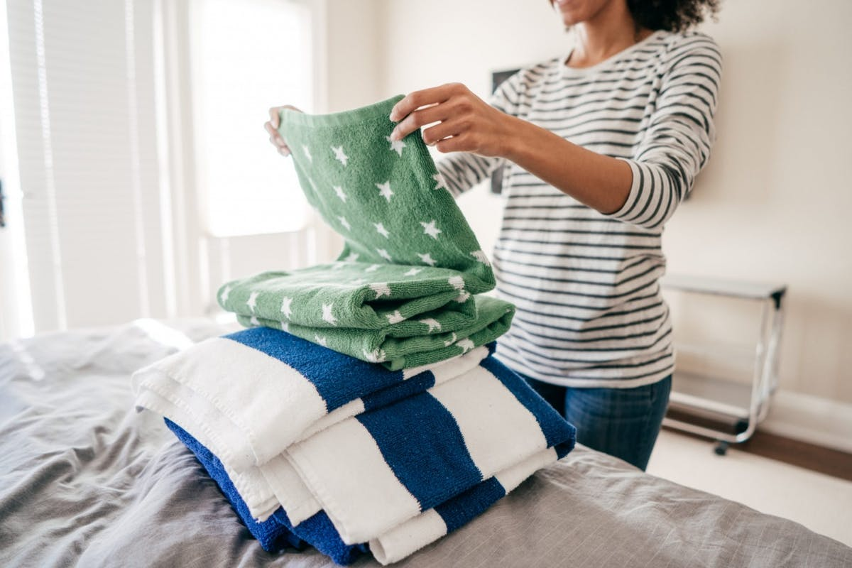 Woman folding towels in her bedroom