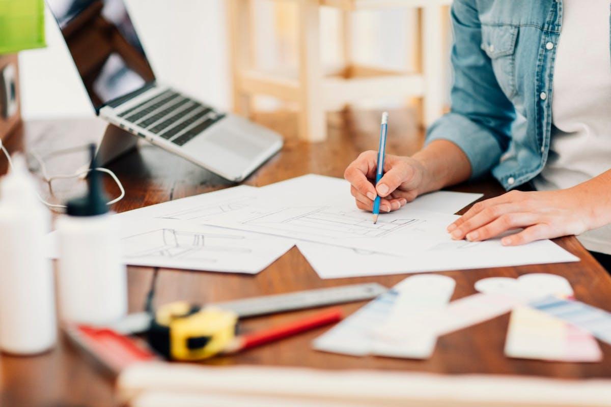 Female furniture designer drawing at a desk in a workshop