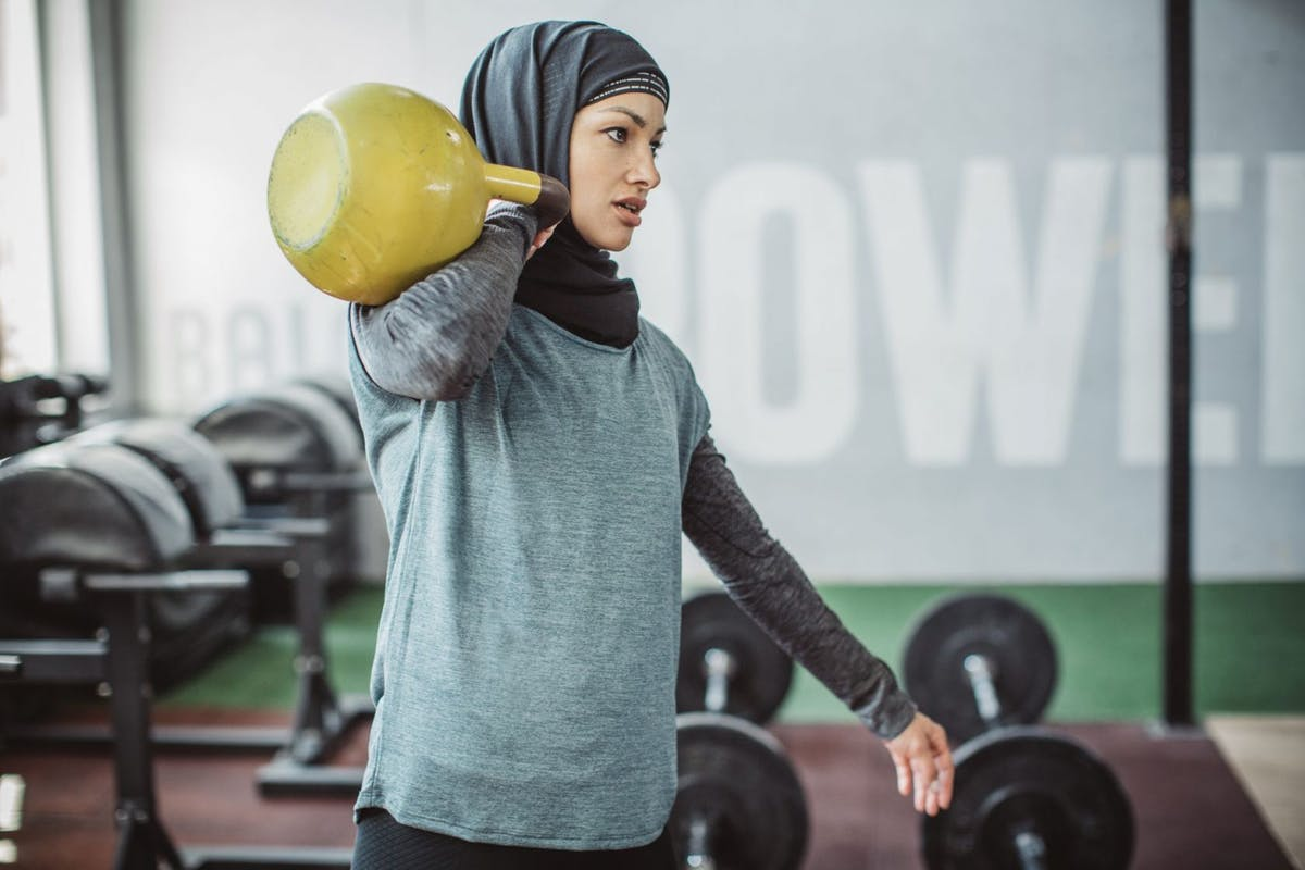A woman holding a kettlebell on her shoulder in the gym.
