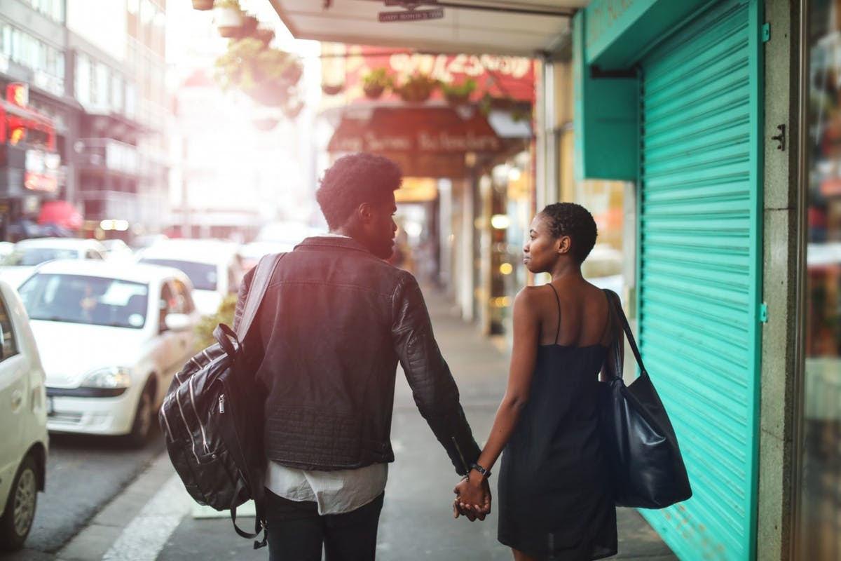 Couple holding hands as they walk down the street