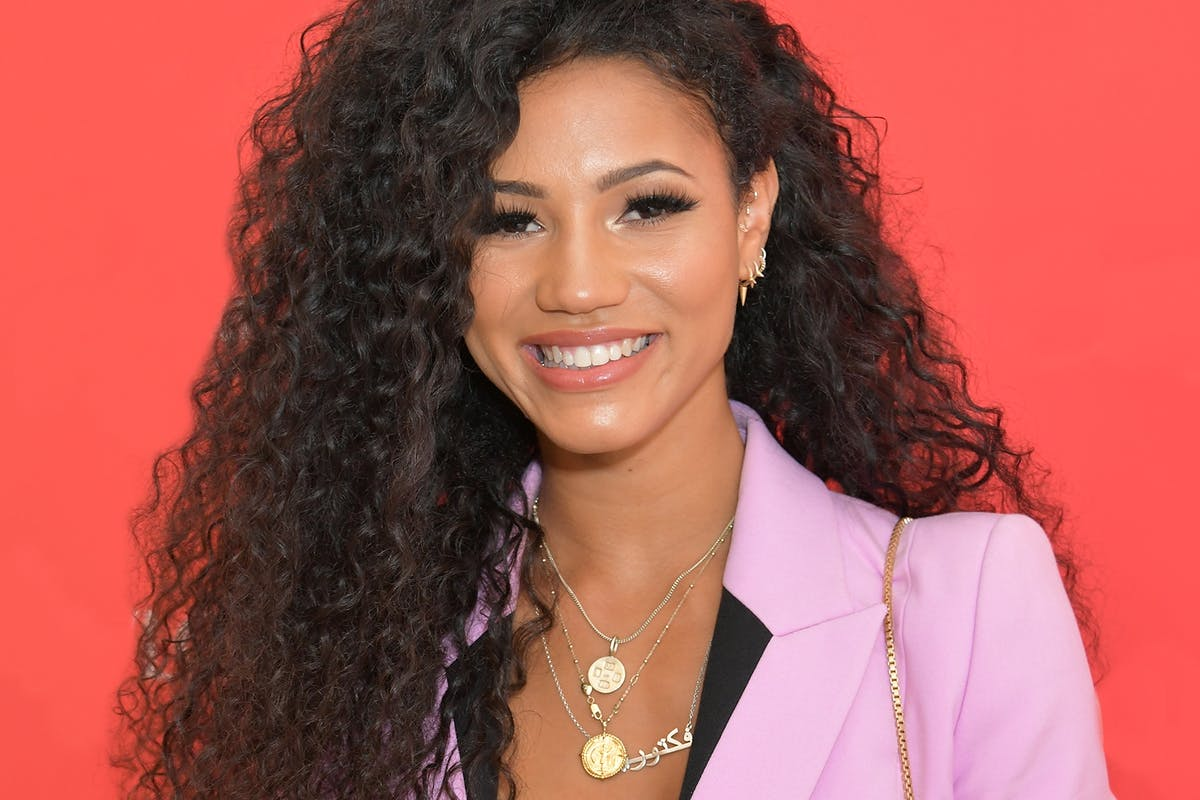 Vick Hope smiling in a pink suit