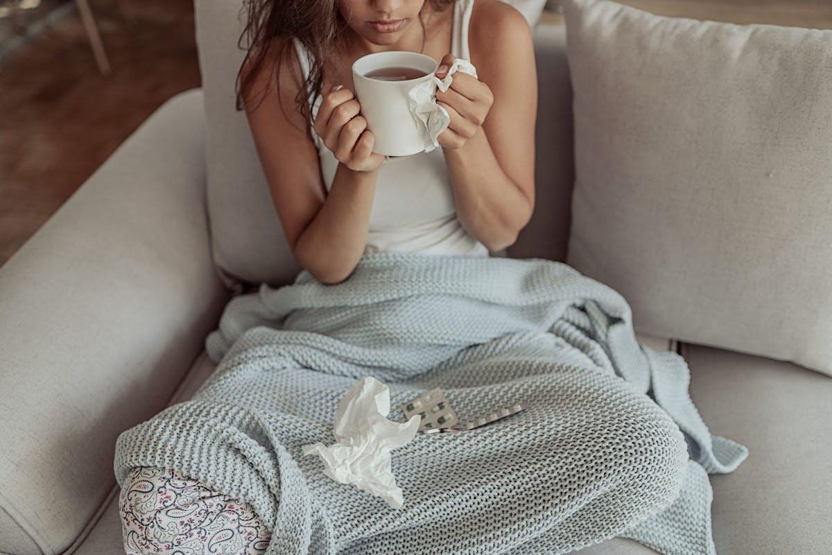 woman pajamas sick ill cold flu tea