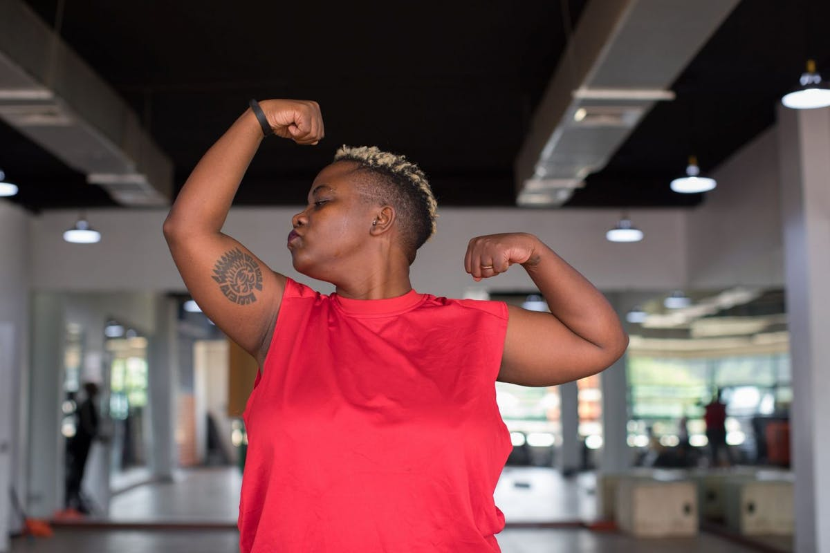 A woman kissing her bicep after training in the gym.
