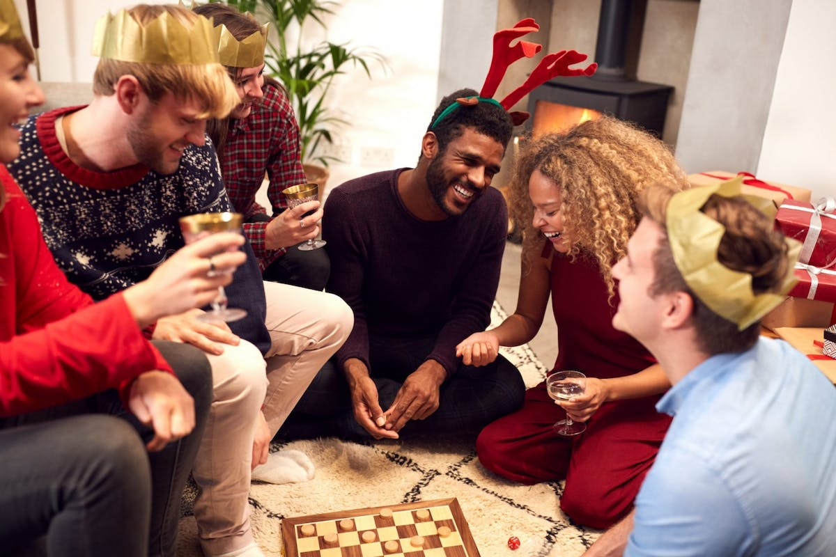 A group of friends playing a board game at Christmas