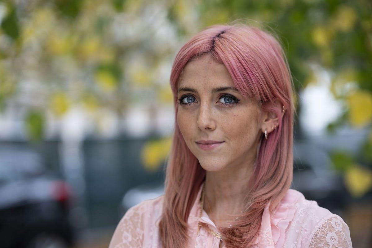 Scarlett Curtis smiling outside with pink hair and shirt