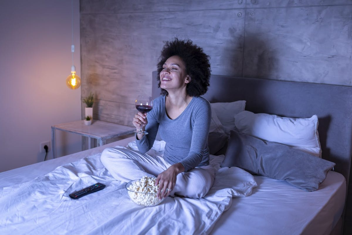 Woman drinking wine watching a movie