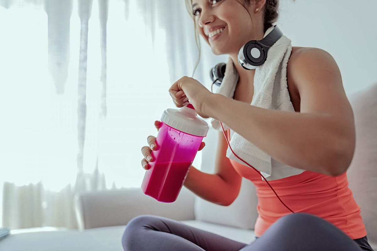A woman drinking a protein shake from a pink bottle after finishing a workout.